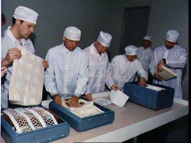 STS-30 clean-suited crewmembers examine locker contents during bench review