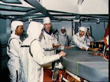 STS-29 crewmembers inspect TDRS-D inertial upper stage (IUS) at KSC VPF