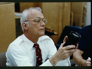 STS-31 Mission Specialist McCandless examines camera lens during JSC briefing