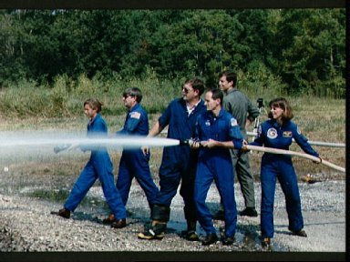 STS-32 crewmembers use water hoses during fire fighting training at JSC