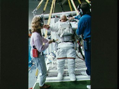 STS-31 MS McCandless dons EMU for JSC EVA underwater simulation in WETF pool
