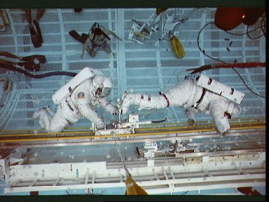 STS-37 crewmembers test CETA hand cart during training session in JSC's WETF
