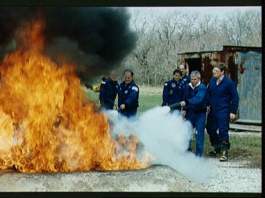 STS-35 crewmembers during fire fighting exercises at JSC fire training pit