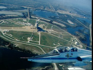 Aerial view of STS-36 Atlantis, OV-104, at KSC LC Pad 39A with T-38A inflight