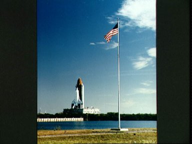 STS-36 Atlantis, OV-104, passes a US flag as it rolls out to KSC LC Pad 39A