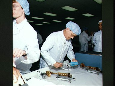 STS-31 MS McCandless inspects HST tools during bench review at Boeing FEPF
