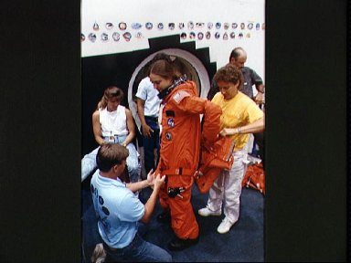 STS-40 MS Jernigan dons LES parachute pack prior to egress training at JSC