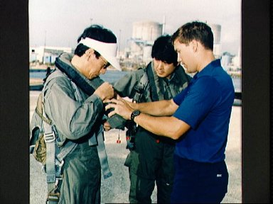 STS-47 Payload Specialist Mohri adjusts life vest during Homestead training