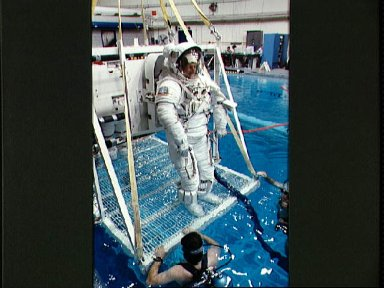 STS-45 MS Foale in EMU is lowered into JSC's WETF pool for underwater test