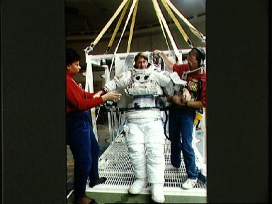STS-45 MS Foale dons EMU with technicians' help in JSC's WETF Bldg 29