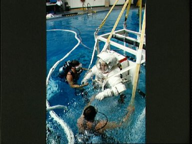 STS-48 MS Buchli, in EMU, is lowered into JSC's WETF pool for EVA simulation
