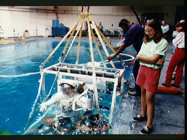 STS-53 MS Voss, in EMU, in lowered into JSC's WETF pool for EVA simulation