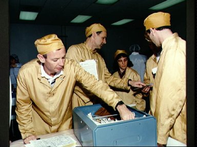 STS-57 crewmembers examine stowage locker contents during bench review