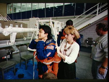 STS-65 Payload Specialist Mukai dons LES and parachute with technicians' help