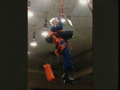 Astronaut Curtis Brown suspended by simulated parachute gear during training
