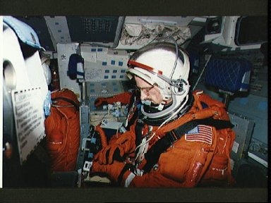 Astronaut Joseph Tanner checks gloves during during launch/entry training