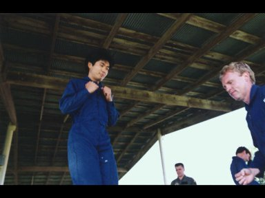 Astronaut candidate Koichi Wakata (left) prepares to jump off a box during a parachute landing demonstration at Vance Air Force Base.
