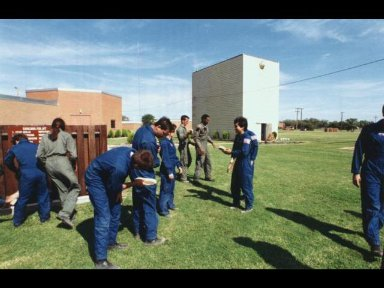 Several 1992 astronaut candidates brush the sand and gravel off one another following one of several phases of parachute familiarization and survival training at Vance Air Force Base in Oklahoma.
