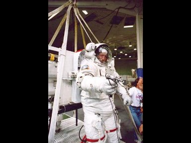 Wearing a training version of the Extravehicular Mobility Unit (EMU) space suit, astronaut Mario Runco, mission specialist, prepares to participate in an underwater rehearsal of a contingency Extravehicular Activity (EVA).