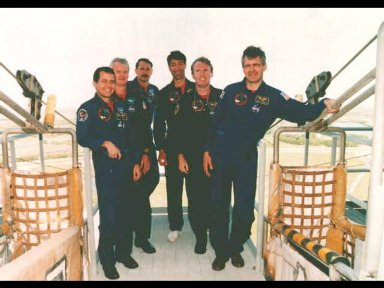 The STS-77 crew take time out from Terminal Countdown Demonstration Test (TCDT) activities to pose for a group portrait next to the slidewire baskets on the emergency egress system at the 195-feet level of Launch Pad 39B, at the Kennedy Space Center (KSC)
