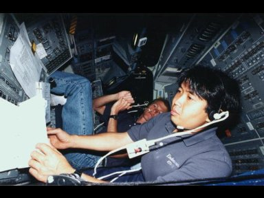 Astronaut Koichi Wakata, representing Japan's National Space Development Agency (NASDA) and assigned as mission specialist for the STS-72 mission, checks over a copy of the flight plan.