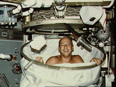 Astronaut Charles Conrad poses in shower facility in crew quarters
