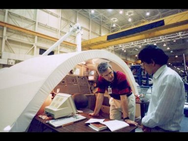 Crew trainer Viet Nguyen briefs Canadian astronaut Marc Garneau, mission specialist, on Remote Manipulation System (RMS) procedures during a training session in the Johnson Space Centers (JSC) Manipulator Development Facility (MDF)
