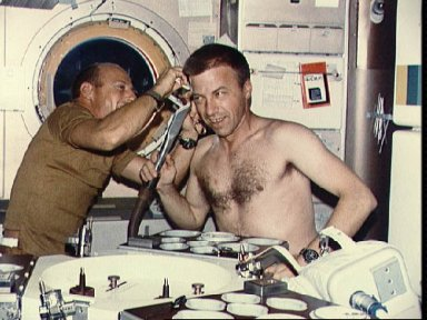 Astronaut Charles Conrad trims hair of Astronaut Paul Weitz