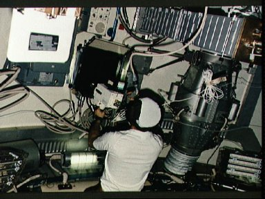 View of Astronaut Owen Garriott taking video of two Skylab spiders experiment
