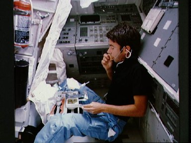 Mission specialist Lenoir takes break to eat his meal