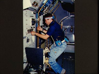 STS-9 payload specialist Byron Lichtenberg attached to portable oscillioscope