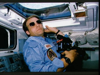 STS-30 MS Lee, wearing sunglasses, uses 70mm camera on aft flight deck