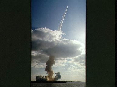 STS-31 Discovery, OV-103, rockets through low-lying clouds after KSC liftoff