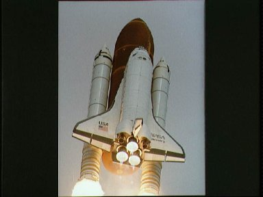 STS-31 Discovery, OV-103, begins its roll maneuver after liftoff from KSC