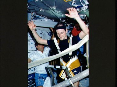 STS-32 crewmembers hold finish line banner as MS Low races on treadmill