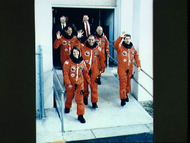 STS-33 crewmembers, wearing LESs, leave KSC O and C Bldg for launch pad