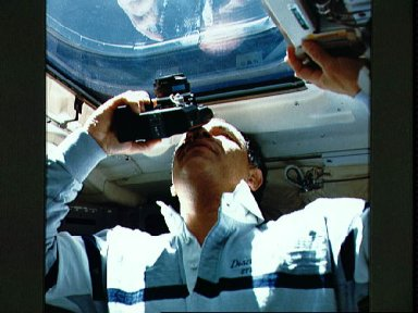 STS-33 Commander Gregory uses 35mm camera to shoot scene outside window W8