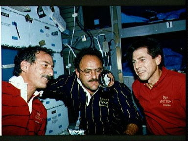STS-35 crewmembers watch a sphere of water float on OV-102's middeck