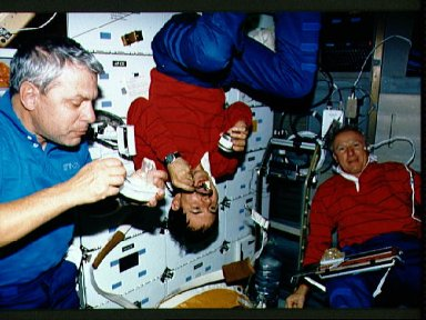 STS-35 crewmembers eat meal on the middeck of Columbia, OV-102