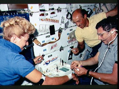 STS-40 crewmembers use inflight blood collection system (IBCS) kit on middeck