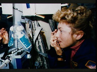 STS-40 Payload Specialist Hughes-Fulford inserts contact lens into her eye