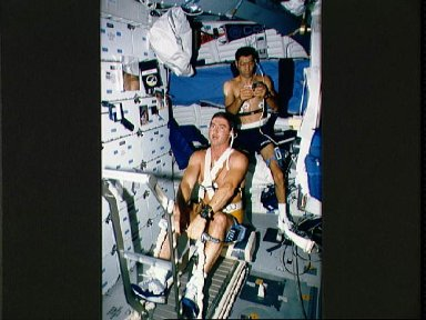 STS-44 crewmembers exercise using treadmill rowing device on OV-104's middeck