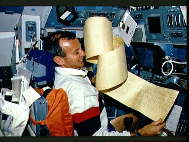 STS-45 Pilot Duffy wrestles with a TAGS printout on OV-104's flight deck