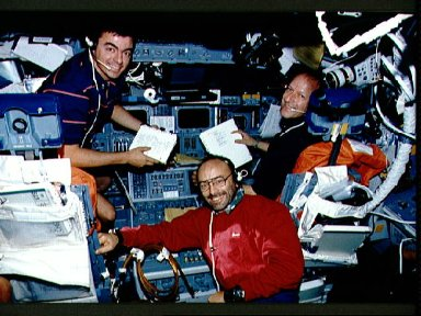 """STS-46 """"blue"""" shift crewmembers look up from work on OV-104's flight deck"""