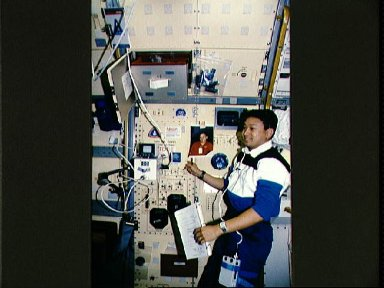 Crewmember in the spacelab in front of the subsystems rack # 4.
