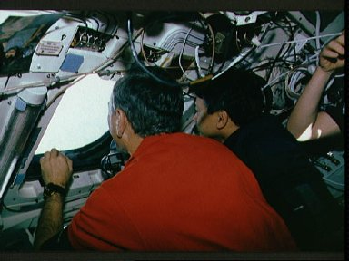 Two male crewmembers in the aft flight deck, looking out the windows.