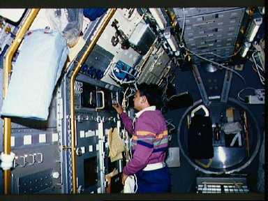 Crewmember working on the spacelab Drop Physics Module, Rack 8.