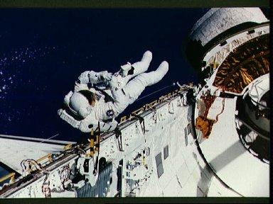 Astronaut James Newman evaluates tether devices in Discovery's payload bay