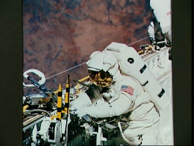 Astronaut James Newman works with power ratchet tool in payload bay
