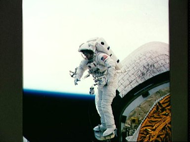 Astronaut James Newman during in-space evaluation of portable foot restraint